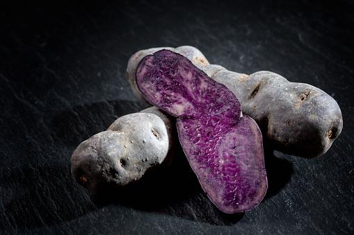 Peruvian Potato「Whole and sliced purple potatoes on slate」:スマホ壁紙(5)