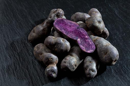 Peruvian Potato「Whole and sliced purple potatoes on slate」:スマホ壁紙(16)