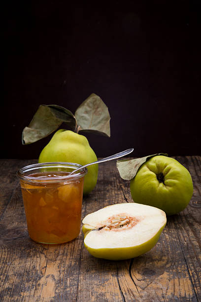 Whole and sliced quinces and a glass of quince jam on wood:スマホ壁紙(壁紙.com)
