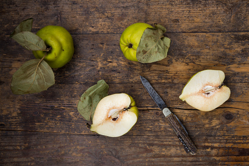 カリン「Whole and sliced quinces and a pocket knife on wood」:スマホ壁紙(1)