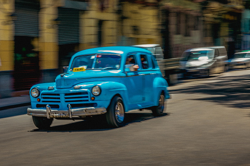 Unrecognizable Person「On a street in Havana, a man is driving an old but well maintained blue American car.」:スマホ壁紙(15)