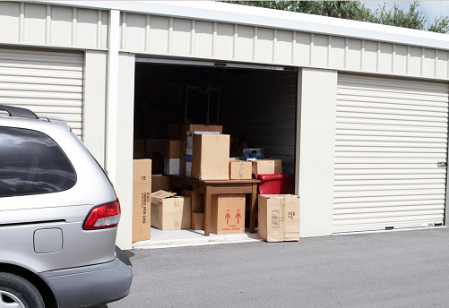 Storage Compartment「An open self storage unit with a van parked next to it」:スマホ壁紙(4)