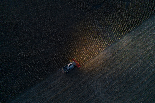 Harvesting「Harvest season. Aerial View of a Combine Harvester gathering the corn crop in the Agricultiral Field After Sunset in Autumn. Agricultural Equipment in Cultivated Land. Nighttime. Working Late.」:スマホ壁紙(2)
