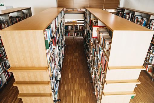 Teenager「Shelves full of books in college wooden library」:スマホ壁紙(18)