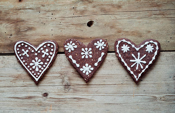 Three gingerbread hearts decorated with sugar icing on wooden table:スマホ壁紙(壁紙.com)