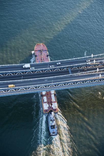USA, New York City, barge sailing underneath Manhattan Bridge on East River, aerial view:スマホ壁紙(壁紙.com)