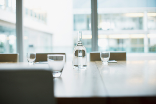 Focus On Background「Carafe and glasses on empty modern conference room in office」:スマホ壁紙(8)