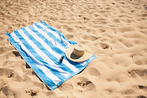 Striped beach towel on sand with hat and glasses:スマホ壁紙(壁紙.com)