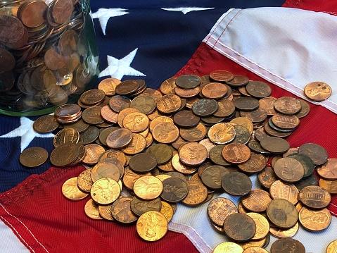 米国硬貨「A jar of American cents, snd one UK penny on an American flag」:スマホ壁紙(1)