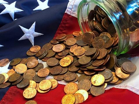 米国硬貨「A jar of American cents, snd one UK penny on an American flag」:スマホ壁紙(0)