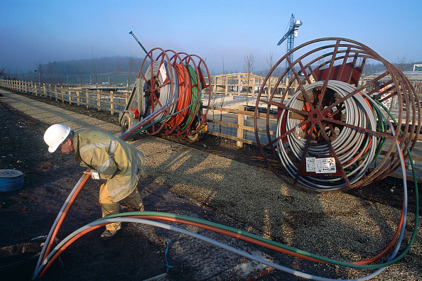 Fiber「Coils of fibre-optic being pushed into ground by a site worker.」:写真・画像(1)[壁紙.com]