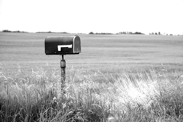 Black and white picture of a mailbox surrounded by fields:スマホ壁紙(壁紙.com)