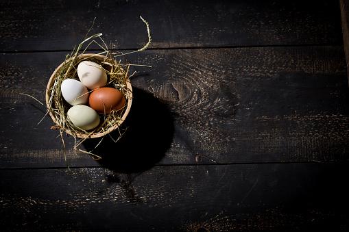イースター「Easter nest with eggs in bowl on dark wood」:スマホ壁紙(6)