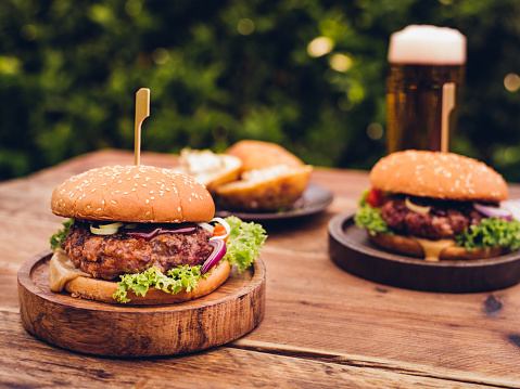 Recipe「Huge gourmet cheese burgers on a rustic wooden table outdoors」:スマホ壁紙(16)