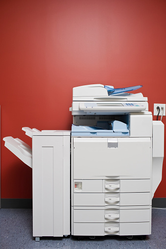 Machinery「Large office photocopier in front of red wall」:スマホ壁紙(4)