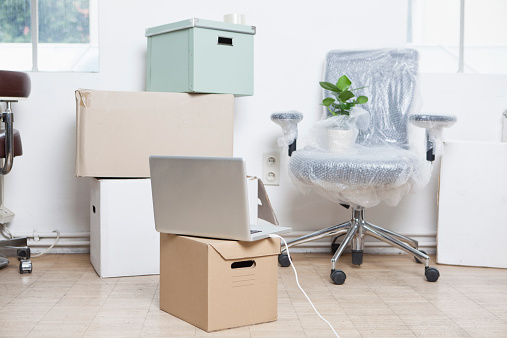 Portability「Stack of cardboard boxes, wrapped swivel chair and a notebook in an office」:スマホ壁紙(13)