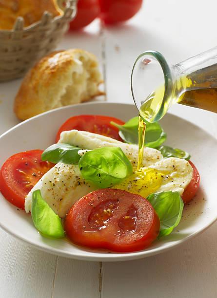 Olive oil pouring on caprese salad in plate, close up:スマホ壁紙(壁紙.com)