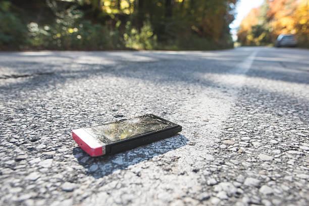 Broken smartphone lying on the road:スマホ壁紙(壁紙.com)