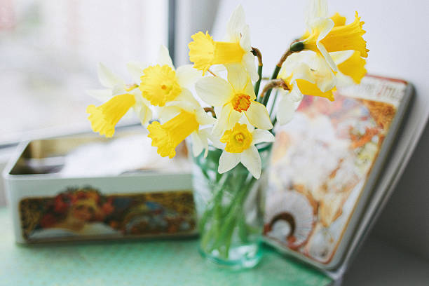 Yellow daffodils in a vase next to a tin:スマホ壁紙(壁紙.com)