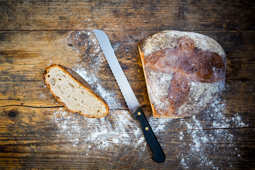 Loaf of Bread「Cut wheat bread powdered with flour and bread knife on dark wood」:スマホ壁紙(10)
