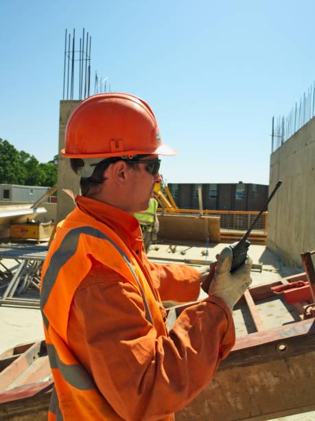 Man holding walkie talkie, positioning glass fibre reinforced (GRC) concrete panel:ニュース(壁紙.com)