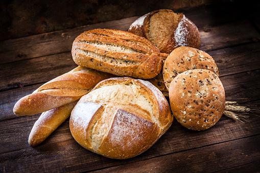 Bun - Bread「Loaves of bread heap shot on rustic wooden table」:スマホ壁紙(16)