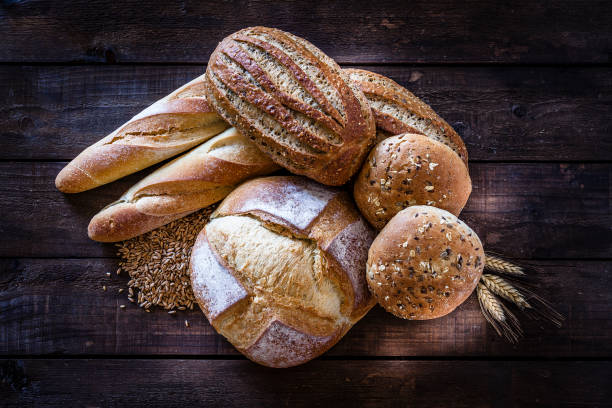 Loaves of bread heap shot on rustic wooden table:スマホ壁紙(壁紙.com)