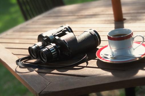 ソーサー「Binoculars and a cup of coffee on table」:スマホ壁紙(0)