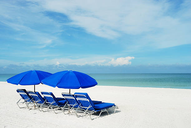 Blue beach umbrellas on a white sandy beach.:スマホ壁紙(壁紙.com)