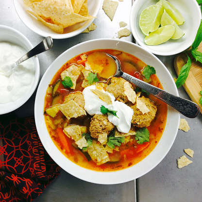 Square「Tortilla turkey meatball soup in a bowl with ingredients around it.」:スマホ壁紙(3)