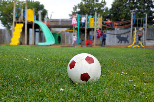 Safety「Soccer Ball Resting on a Green Grass at the Playground」:スマホ壁紙(12)