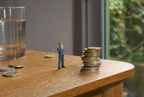 Figurine「miniature man looking at pile of coins on table」:スマホ壁紙(15)