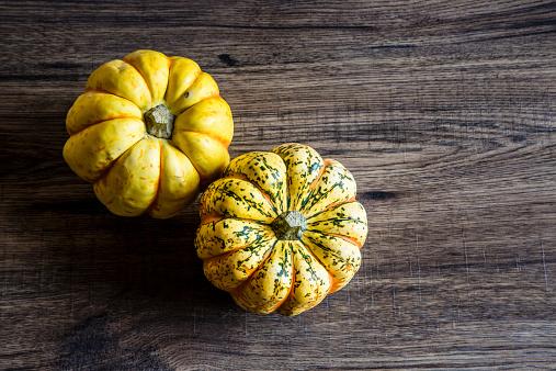 かぼちゃ「Two chameleon pumpkins on dark wood」:スマホ壁紙(7)