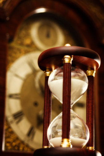 Sepia Toned「Antique hourglass with grandfather clock face in background.」:スマホ壁紙(16)