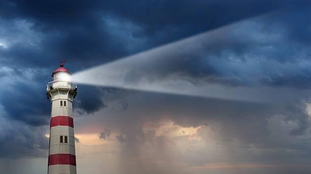Partly sunlit lighthouse, bad weather in background:スマホ壁紙(壁紙.com)