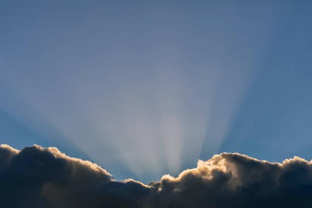 Sunbeams emerge from behind a cloud in a blue sky:スマホ壁紙(壁紙.com)