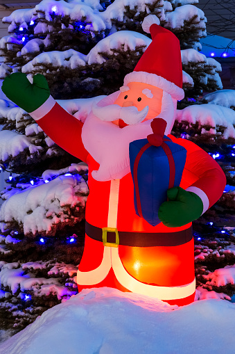 Christmas「Glowing inflated Santa Claus Christmas decoration with Christmas lights on a snow covered evergreen tree」:スマホ壁紙(8)