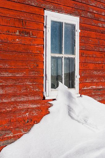 雪景色「A snow drift touching the window along a building with a red painted wooden facade that is worn and weathered」:スマホ壁紙(0)