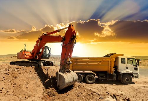 Construction Vehicle「Excavator loading dumper trucks at sunset」:スマホ壁紙(11)