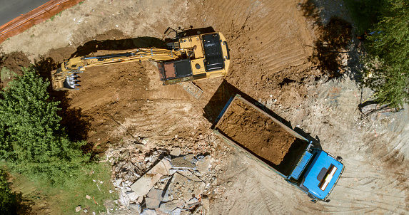 Construction Vehicle「Excavator loading dug out soil onto truck at building site」:スマホ壁紙(3)