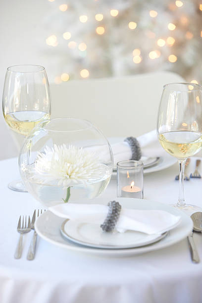 Glasses of white wine and centerpiece beside place setting on table:スマホ壁紙(壁紙.com)