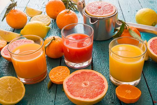 Juice - Drink「Glasses of orange juice, grapefruit juice and multivitamine juice, juice squeezer and fruits on wood」:スマホ壁紙(3)