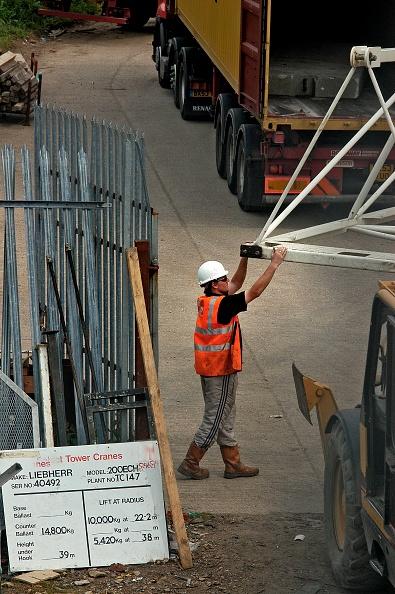 Mid Adult Men「Banksmen unloading crane from truck on construction site, London, UK」:写真・画像(12)[壁紙.com]