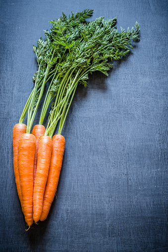 Carrot「Fresh carrot bunch with copy space on dark gray textured background」:スマホ壁紙(9)
