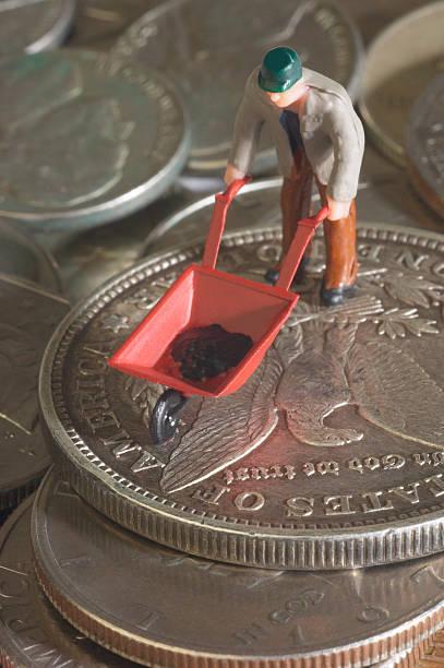 Figurine with miniature wheelbarrow on pile of coins:スマホ壁紙(壁紙.com)