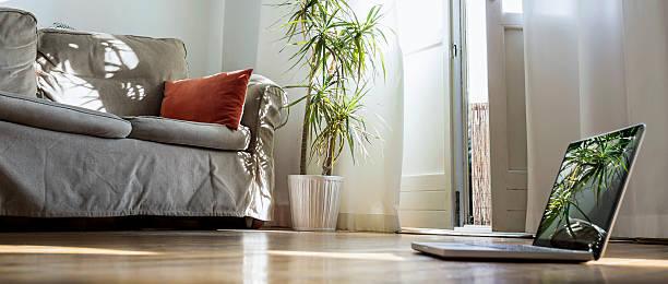 Laptop standing on wooden floor in a living room:スマホ壁紙(壁紙.com)