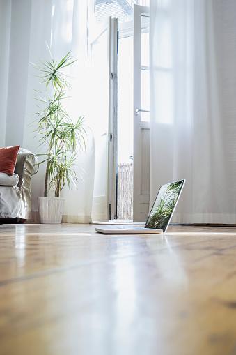 Curtain「Laptop standing on wooden floor of a living room」:スマホ壁紙(5)