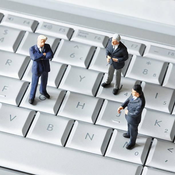 Artificial businessmen are standing on a keyboard of a PC.:スマホ壁紙(壁紙.com)