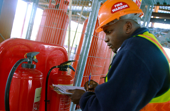 Insurance「Fire warden checking the fire extinguisher unit on a construction site」:写真・画像(1)[壁紙.com]
