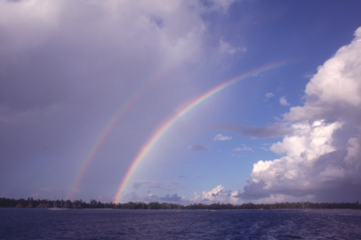 Rainbow「View of storm clouds as two rainbows arch over the horizon. French Polynesia, Rangiroa Tuamotus.」:スマホ壁紙(15)